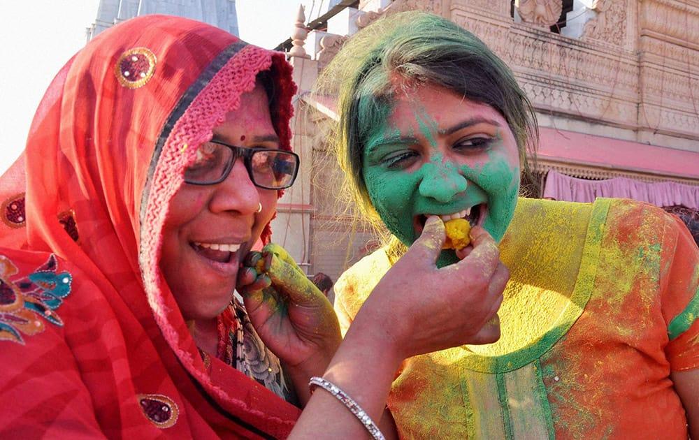 Women enjoying ladoo during Latthmaar holi celebration in Barsana near Mathura.
