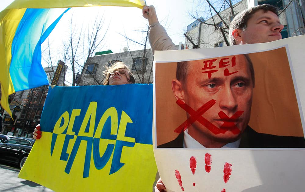 Ukrainians stage a rally to denounce Russia's President Vladimir Putin and his military presence in Ukraine's Crimea region, in Seoul, South Korea. The Korean word at right read `Putin`.