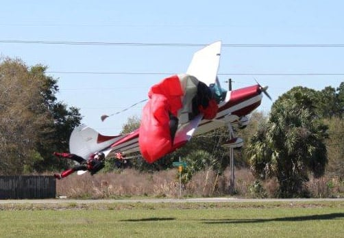 This photo released by the Polk County Sheriff`s Office shows a plane getting tangled with a parachutist, at the South Lakeland Airport in Mulberry, Fla. Both the pilot and jumper hospitalized with minor injuries.