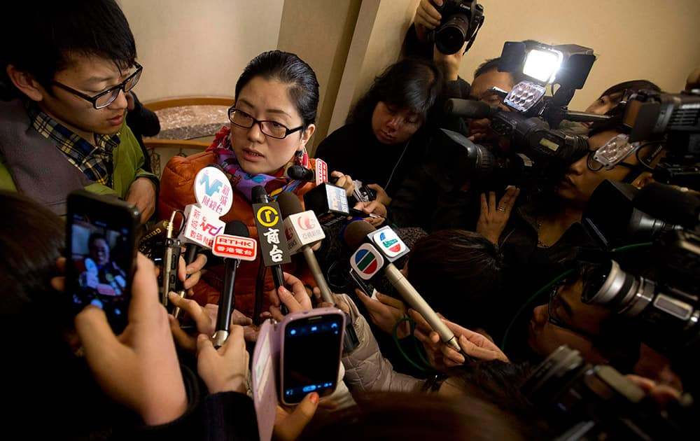 A Chinese woman who identified herself as Miss Nan, whose husband and brother where among the passengers aboard a missing Malaysia Airlines plane speaks to the media outside a hotel room for relatives or friends of passengers aboard the missing airplane, in Beijing, China.