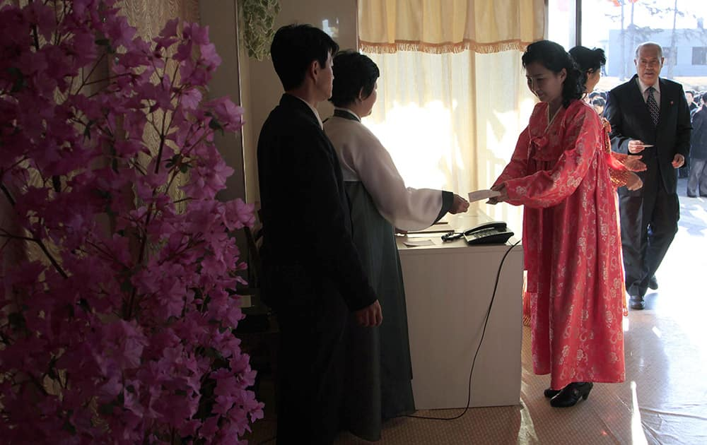 A woman receives a ballot to vote to elect deputies to the 13th Supreme People`s Assembly in Pyongyang, North Korea.
