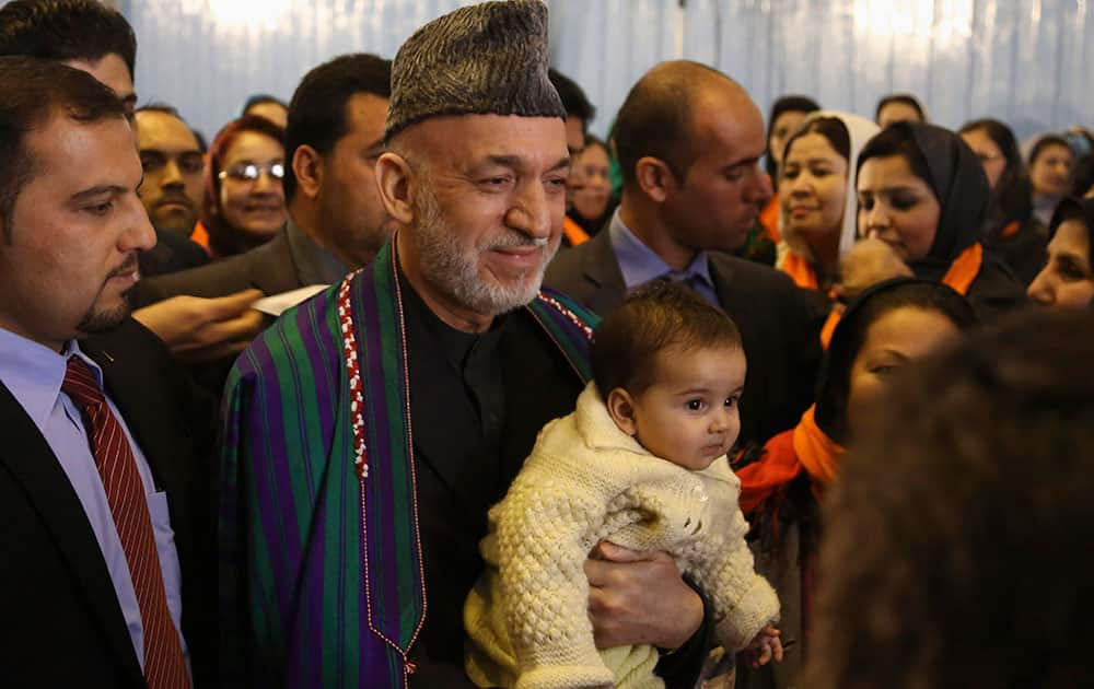 Afghan President Hamid Karzai, center, poses for a picture with a child he picked up from the crowd after delivering a speech on the occasion of the International Women`s Day at the Armani school in Kabul, Afghanistan.