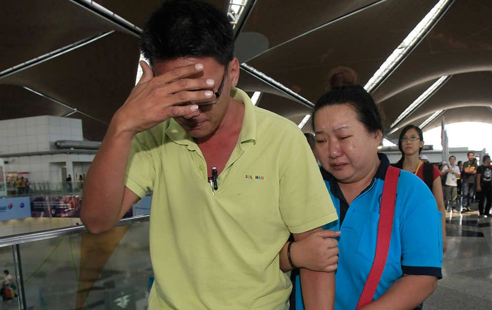 A woman cries as she walks out of the reception center and holding area for family and friend of passengers aboard a missing Malaysia Airlines plane, at Kuala Lumpur International Airport in Sepang, outside Kuala Lumpur, Malaysia.