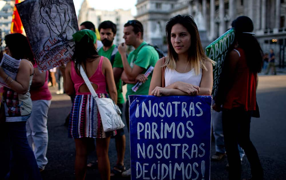 A woman holds a banner that reads in Spanish We give birth, we decide during a rally in Buenos Aires, Argentina.