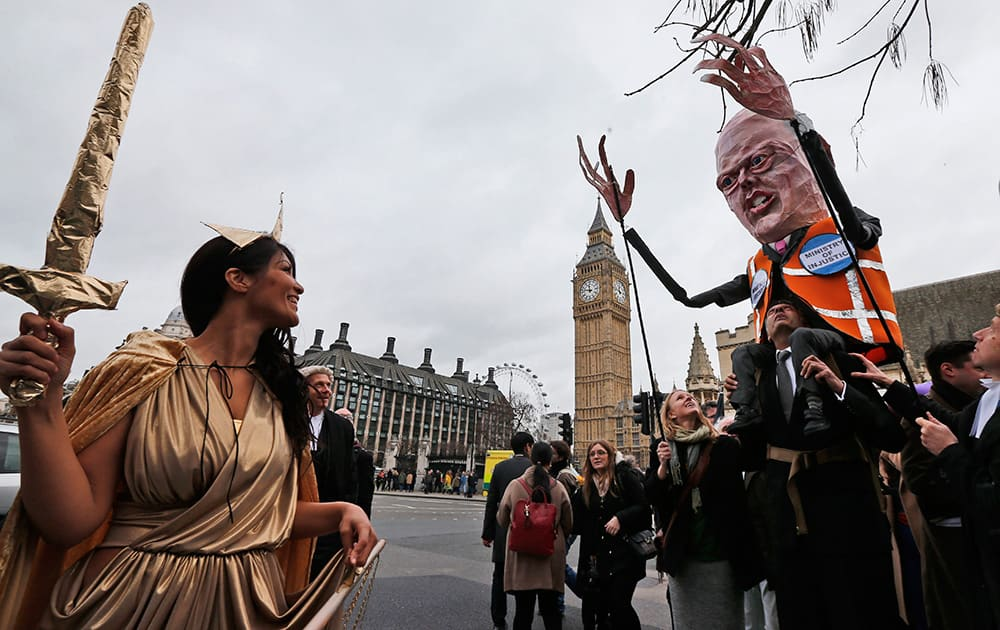 Lawyers, one dressed as Justice and one carrying a puppet depicting Chris Grayling, Britain`s Justice Secretary march to protest against legal aid cuts, across from the Houses of Parliament in central London.