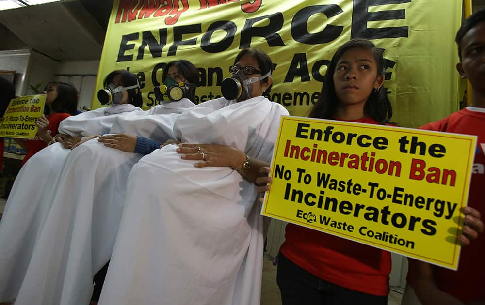 Filipino activists dressed as pregnant women wearing gas mask pose during a protest as part of their observance of International Women`s Day in suburban Quezon city, north of Manila, Philippines.