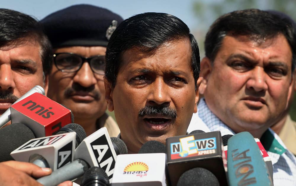 Arvind Kejriwal addresses media before leaving to meet Gujarat state Chief Minister Narendra Modi, in Ahmadabad.