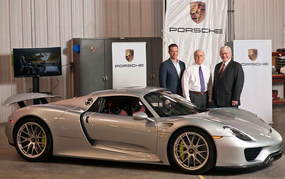 This photo provided by the Georgia Ports Authority, Port of Brunswick Global Manager, Bill Jakubsen, Port of Brunswick General Manager of Operations Bill Dawson and Porsche`s Manager of Vehicle Logistics and Port Operations Justin Newell, stand near the first shipment of Porsche 918 Spyder automobile at the the Georgia Ports Authority Colonel's Island Terminal at the Port of Brunswick.