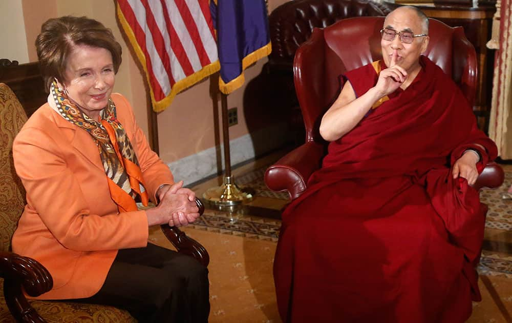Tibetan spiritual leader the Dalai Lama gestures towards a reporter asking a question as he meets with House Speaker John Boehner of Ohio and House Minority Leader Nancy Pelosi of Calif., on Capitol Hill in Washington.