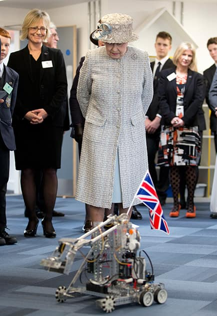 Britain`s Queen Elizabeth II looks at a robotic demonstration as she visits Reed`s School, in Cobham, England.