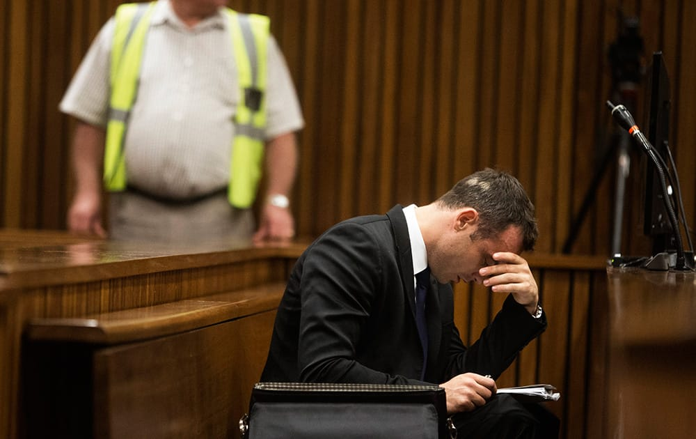Oscar Pistorius, right, places his hand over his eyes while sitting in court on the fourth day of his trial at the high court in Pretoria, South Africa.