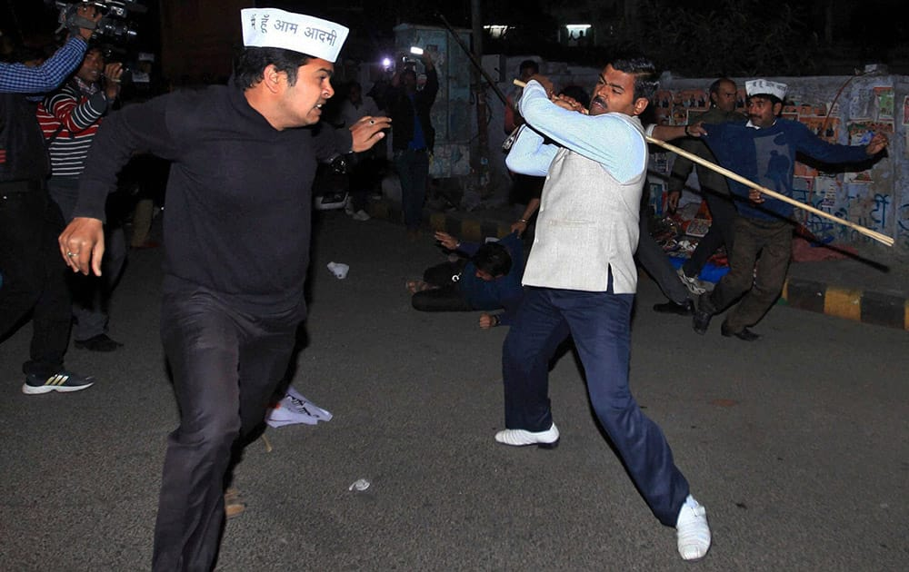 Activists of India's opposition Bharatiya Janata Party (BJP) and those of Aam Aadmi Party, or Common Man`s Party, wearing white caps clash in Lucknow.