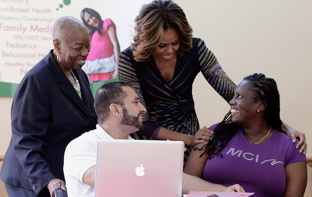 First Lady Michelle Obama talks to Affordable Care Act enrollee Kalenthia Nunnally, right, as Annie Neasman, left, and certified application counselor Paul Andres Salazar, second from left, look on at the Jessie Trice Community Health Care Center in Miami.