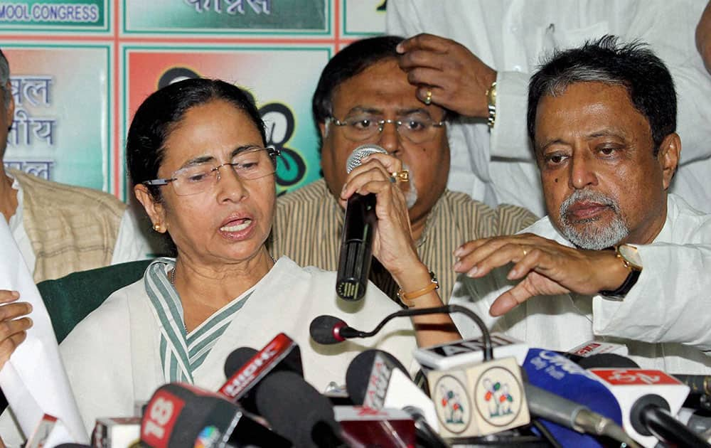 Trinamool Congress Supremo and West Bengal Chief Minister Mamata Banerjee with State Finance Minister Amit Mitra( L)Formar Railway Minister and TMC General Sccretary Mukul Roy (R) announces candidates forLok Sabha elections at a press conference in Kolkata.