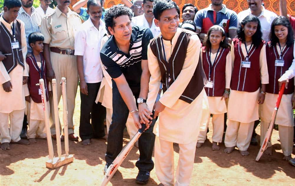 Sachin Tendulkar, Brand Ambassador, UNICEF South Asia Region, demonstrates batting techniques to visually impaired children at a blind school near Mandangad in Ratnagiri district.