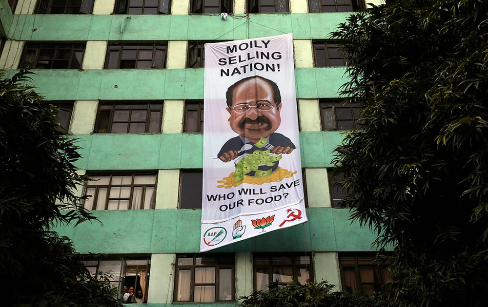 Greenpeace activists hang a giant banner with a caricature of Indian Minister for Environment and Forest Veerappa Moily on his office building as a sign of protest in New Delhi. The activists were protesting the Indian government's decision to permit multinational seed companies field trial of genetically modified crops across the country.