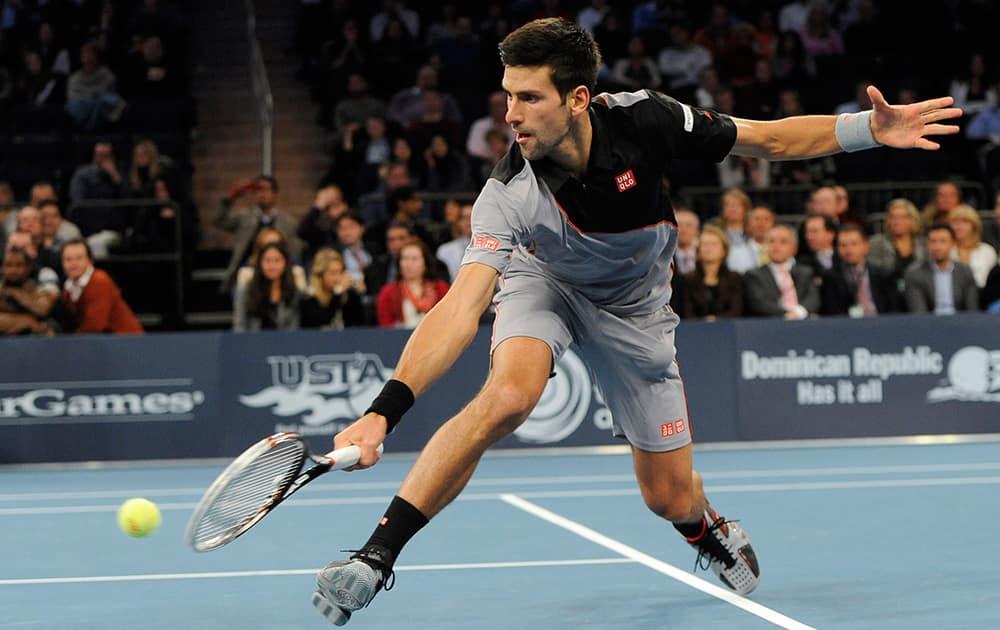 Novak Djokovic stretches to return against Andy Murray in the BNP Paribas Showdown Tennis Tournament.