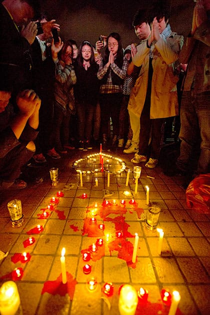 People light up candles and pray for the victims on a square outside the Kunming Railway Station where more than 10 assailants slashed scores of people with knives the night before in Kunming, in western China`s Yunnan province.