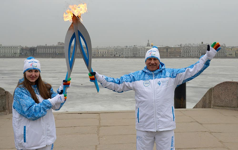 This photo provided by www.sochi2014.com torch bearers hold their torches during the Paralympic torch relay with a frozen Neva River at the background in St.Petersburg, Russia.