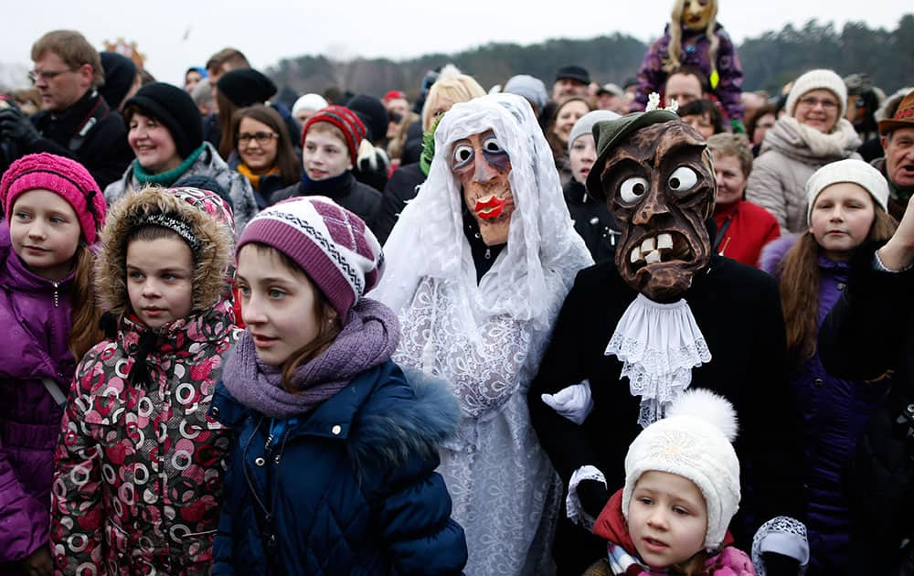 People gather watch an effigy of Lady Winter burning, with one couple wearing traditional carnival masks, during Shrovetide celebrations, in the Rumsiskes village, some 89 kilometers (56 miles) north of Vilnius, Lithuania.