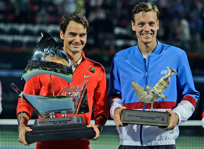 Roger Federer of Switzerland, left, and Tomas Berdych of Czech Republic display their trophies after Federer won the final match of the Dubai Duty Free Tennis Championships in Dubai, United Arab Emirates.