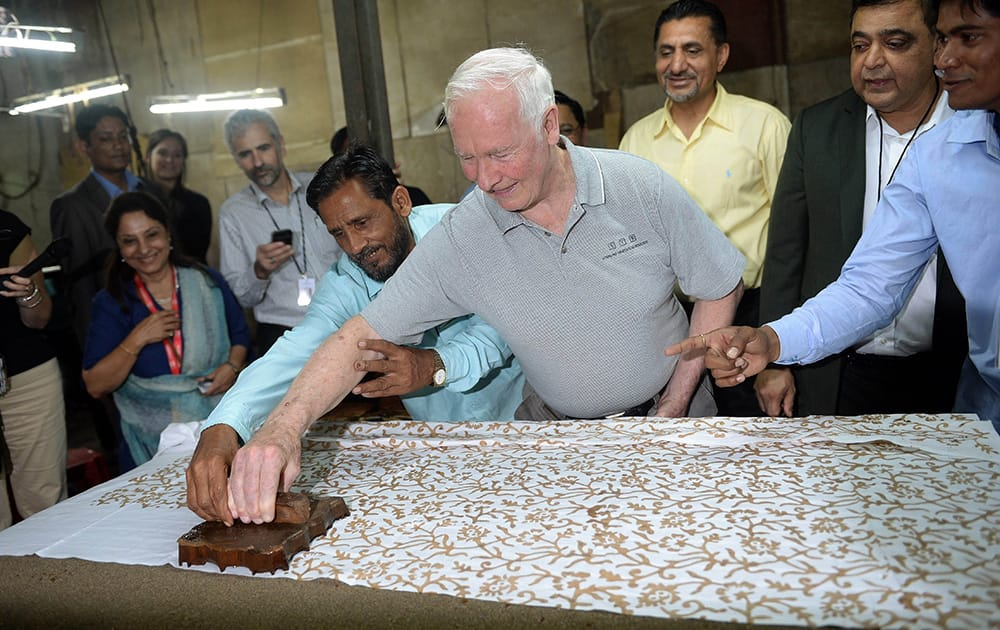 Canada`s Governor General David Johnston tries his hand at block printing with an Indian worker at a small factory in the Dharavi slum area of Mumbai.