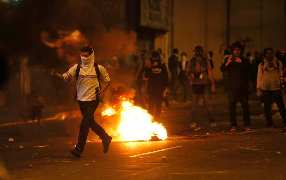 A demonstrator runs to confront a line of Bolivarian National Guard officers during anti-government protests in Caracas, Venezuela.