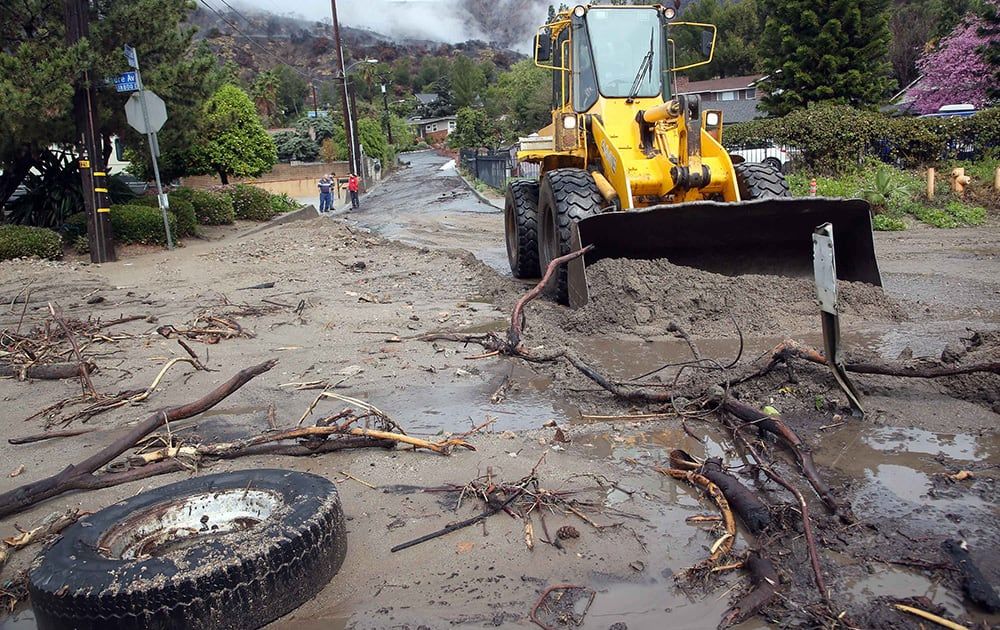 Glendora city workers clear mud and debris from the hills, in Glendora, Calif. The first wave of a powerful Pacific storm spread rain and snow early Friday through much of California, where communities endangered by a wildfire just weeks ago now faced the threat of mud and debris flows.