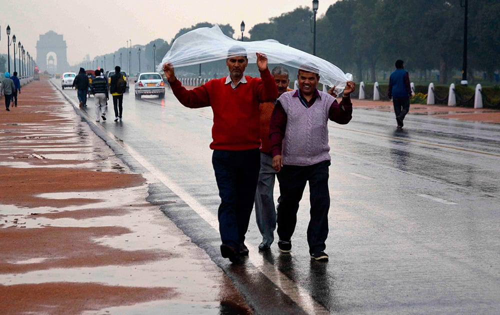 People walk with a plastic sheet during rains in New Delhi.