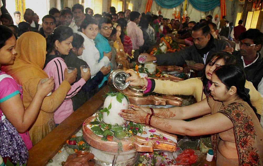 Devotees offer milk to perform ritual on Shivratri celebration in Allahabad.