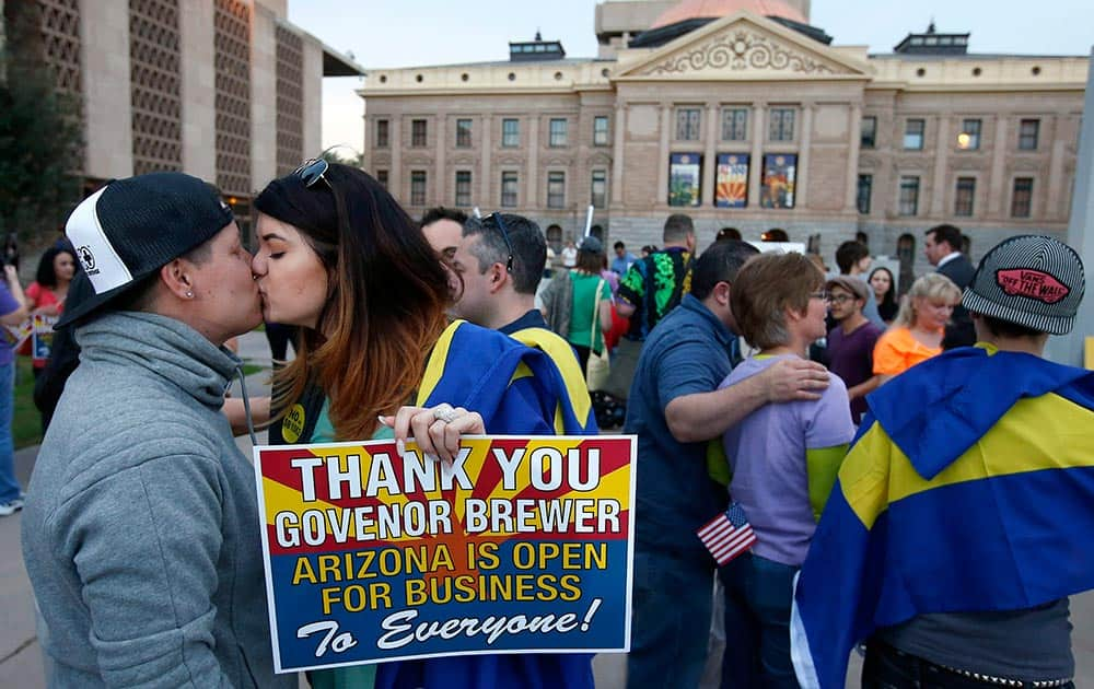 With the Arizona Capitol in the background, gay rights supporters Rachel Butas and Jo Jo Halko kiss after the two learn that Arizona Gov. Jan Brewer announces she has vetoed SB1062, a bill designed to give added protection from lawsuits to people who assert their religious beliefs in refusing service to gays, in Phoenix.