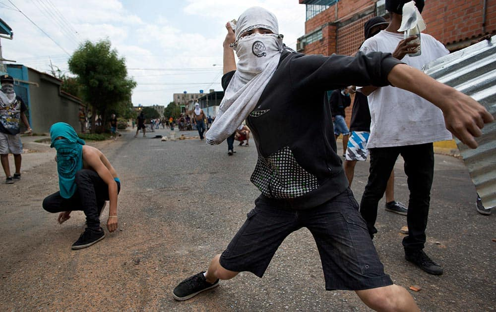 A masked demonstrator throws a rock at riot police during an anti-government protest in Valencia, Venezuela.