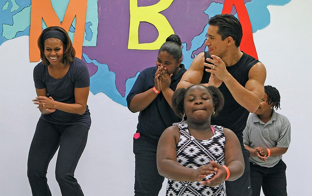 First lady Michelle Obama laughs as she participates in a zumba class with Mario Lopez at a Miami parks and recreation center during a visit to promote her `Let`s Move` campaign.