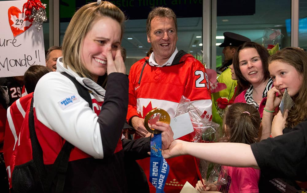 Canadian Olympic women`s hockey gold medallist Marie-Philip Poulin, left, wipes her eyes as she is welcomed by family members when arriving from the Sochi Winter Olympics, at the Jean-Lesage Airport in Quebec City. Poulin`s father Robert, behind, looks on.