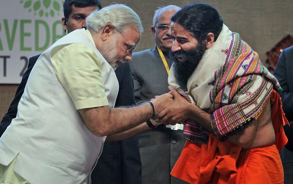 Narendra Modi presents a shawl as he greets yoga guru Baba Ramdev during the National Ayurvedic Summit in Gandhinagar.