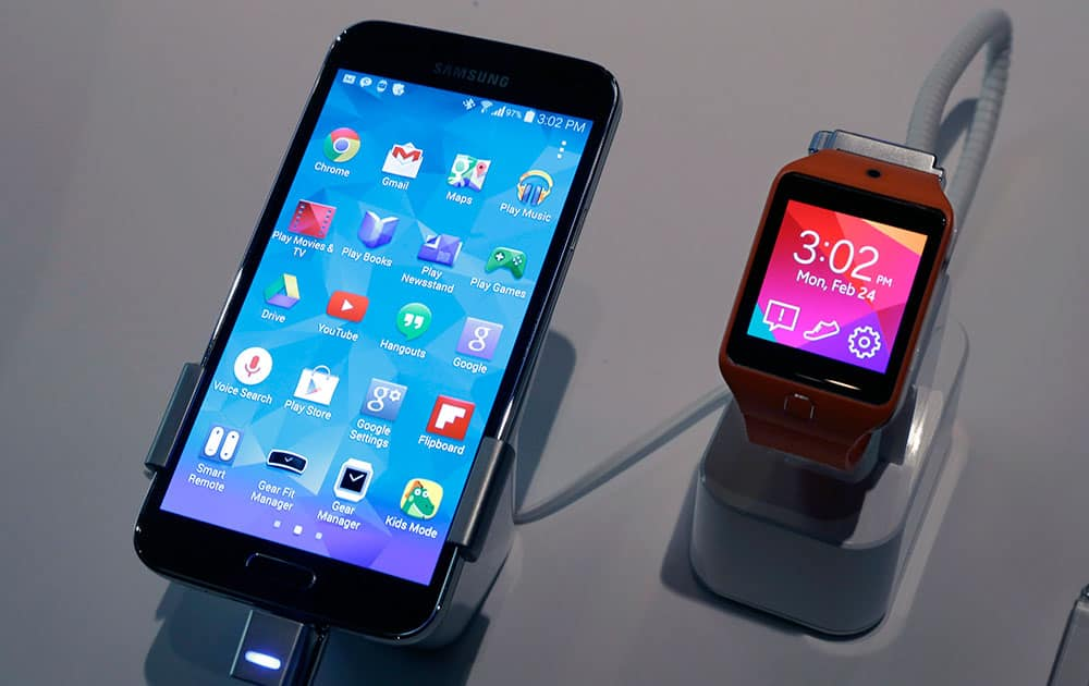 A Samsung Galaxy S5 smartphone, left, and a Samsung Gear 2 are displayed at the Samsung Galaxy Studio, in New York.