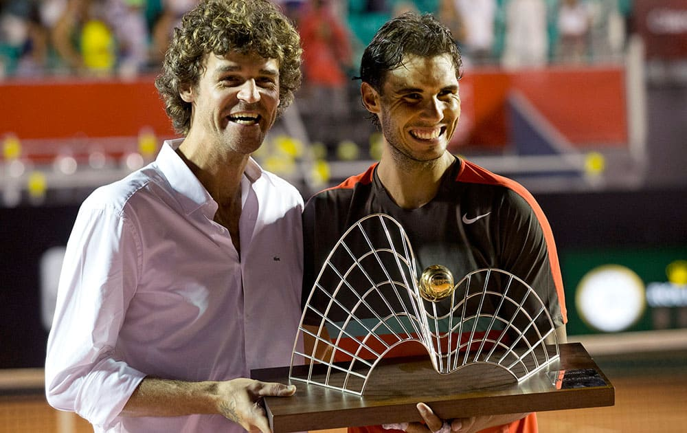Spain`s Rafael Nadal, right, and Brazil`s former tennis player Gustavo Kuerten pose for a photo with Nadal`s trophy at the end of the Rio Open tournament in Rio de Janeiro, Brazil. Nadal returned from a troublesome back injury to win the Rio Open.