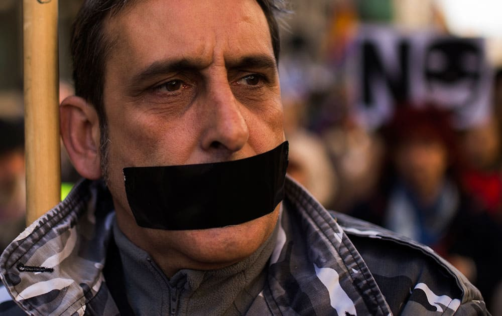 Protester marches with his mouth taped during a pro-civil rights demonstration in Madrid.