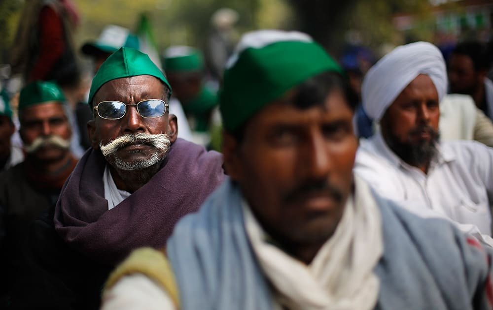 Farmers listen to a speaker as they participate in a protest near the Indian Parliament in New Delhi. The farmers were protesting against government procuring land for setting up industries and not providing enough subsidy to farmers among several other grievances.