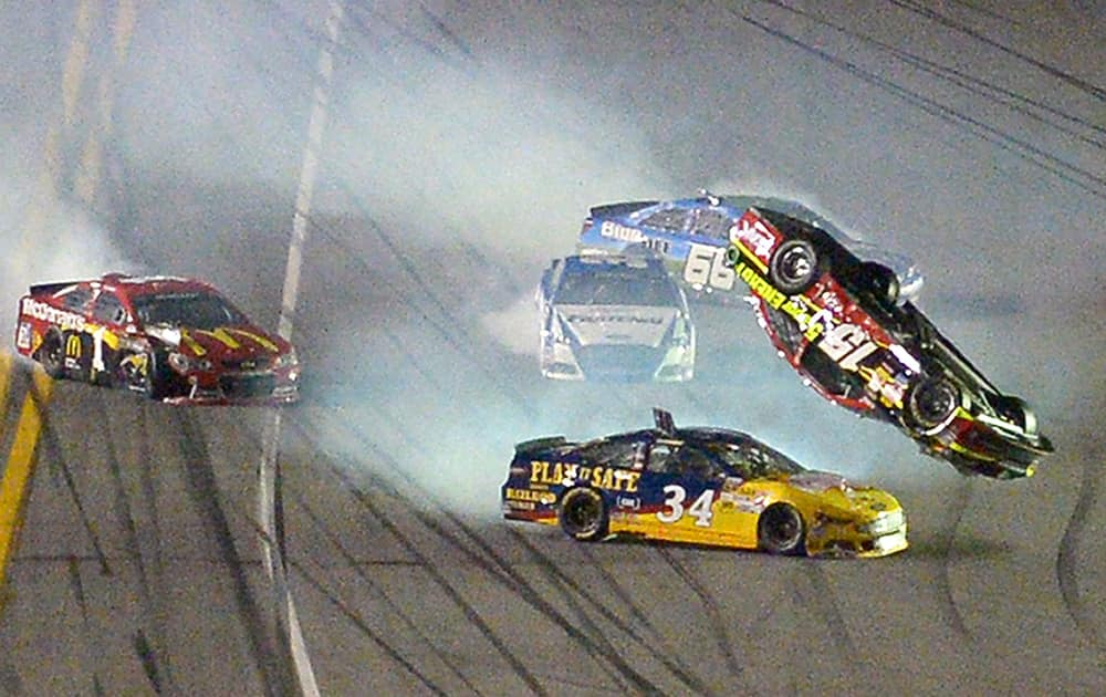 Clint Bowyer (15) flips over David Ragan (34) after a collision coming out of Turn 4 during the second of two NASCAR Sprint Cup qualifying auto races at Daytona International Speedway in Daytona Beach, Fla.