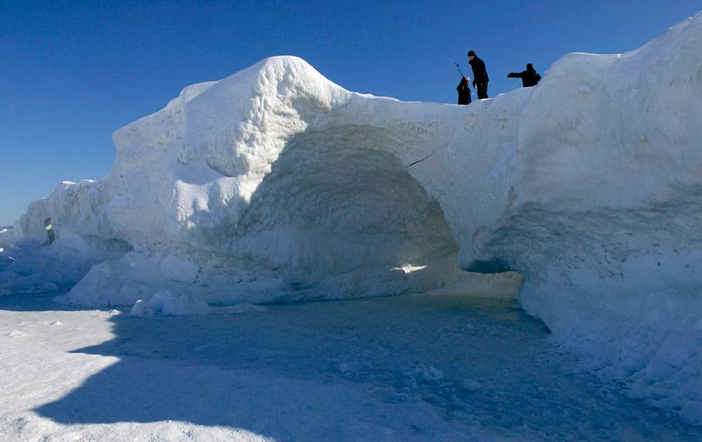 People look at an ice cave at Lake Michigan along the shore of northern Leelanau County, between Northport and Leland, Mich.