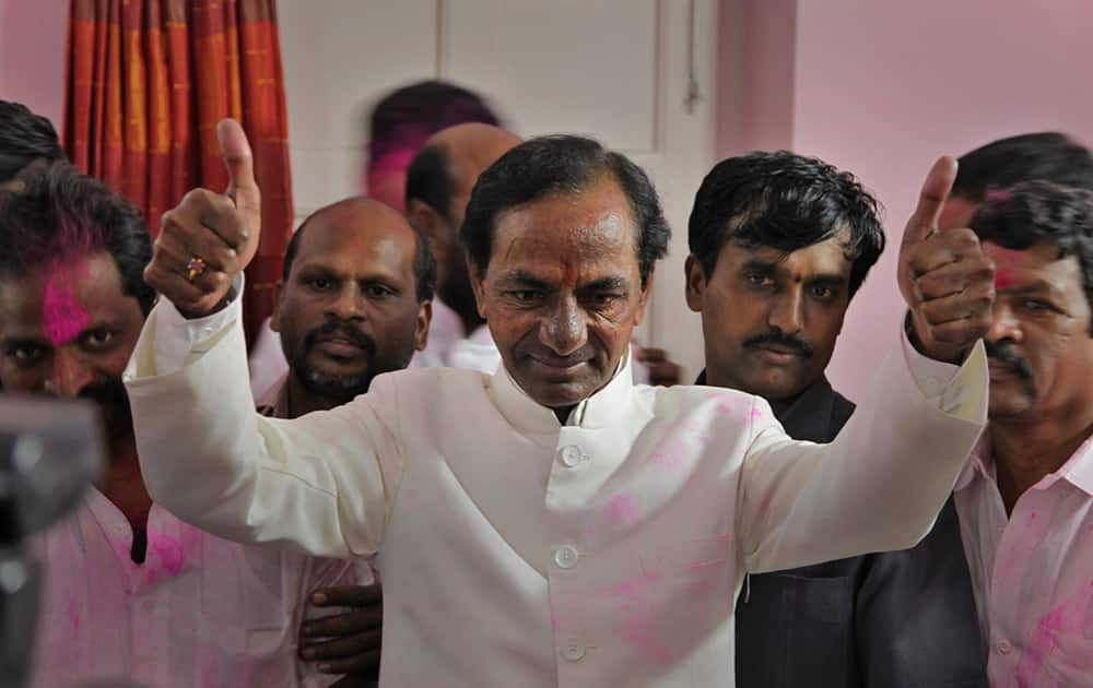 Telangana Rashtra Samithi (TRS) party president K. Chandrashekar Rao shows a thumbs up sign to supporters after the Indian parliament's lower house passed the bill for the creation of new state called 'Telangana' in New Delhi.