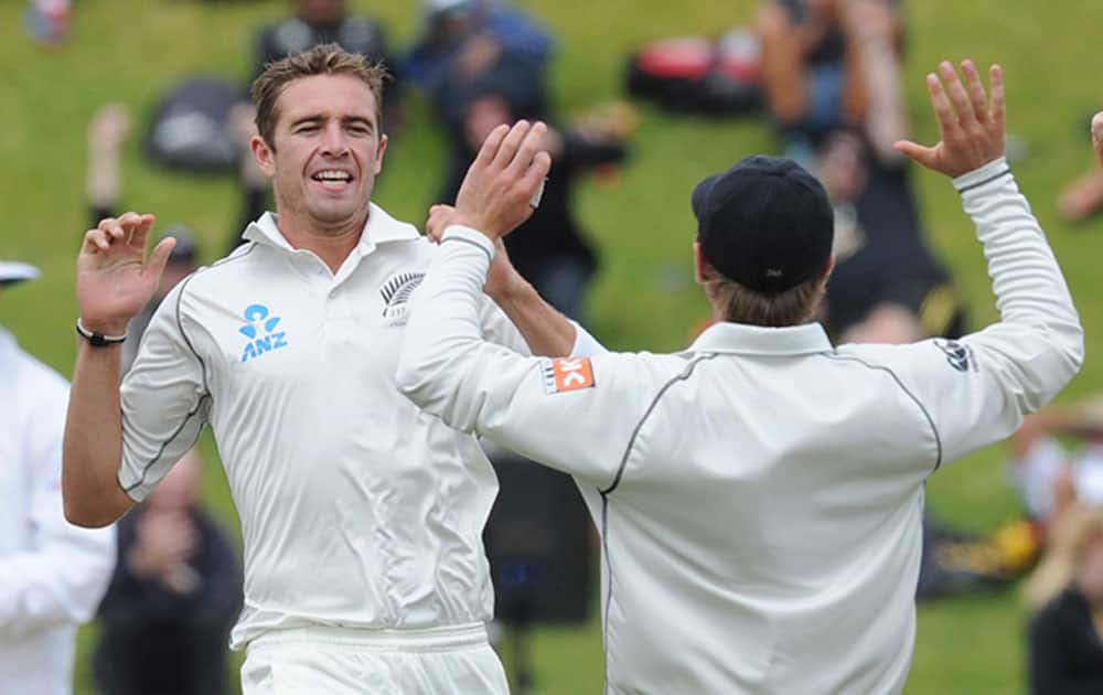 New Zealand's Tim Southee, left, celebrates with Tom Latham after dismissing India's Murali Vijay for 7 on the final day of the second test at the Basin Reserve in Wellington, New Zealand.