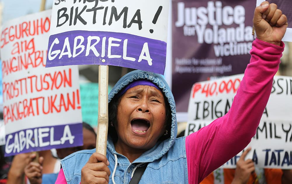 Typhoon Haiyan victims and supporters shout slogans as they march towards the Malacanang presidential palace in Manila, Philippines. super typhoon killed more than 6,200 people in last November.