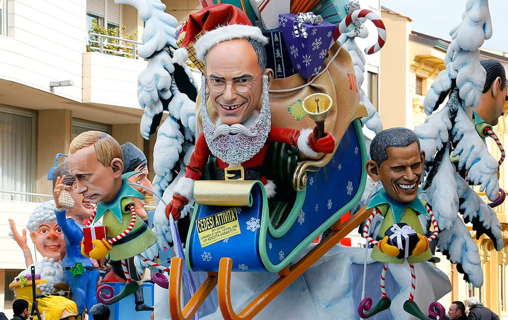 A float depicting former Premier Enrico Letta, center, dressed as Santa Klaus on sledge with a sign reading in Italian `Going out of business`, US President Barack Obama, right, and Russian President Vladimir Putin, left, parades at the traditional Viareggio Carnival, in Viareggio.