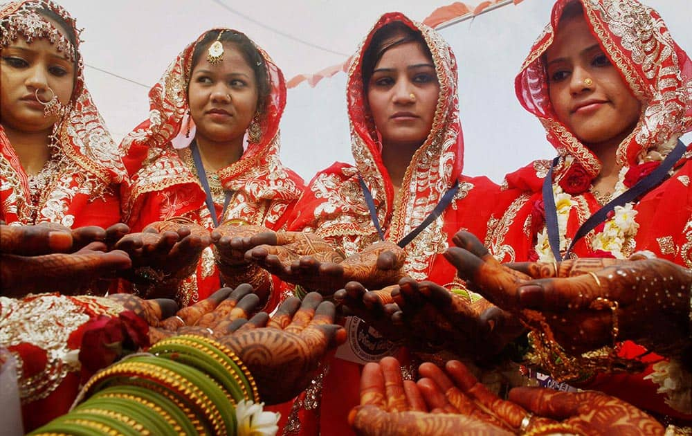 Brides from the Muslim community showing their heena decorated hands during a mass marriage ceremony in Ahmedabad.