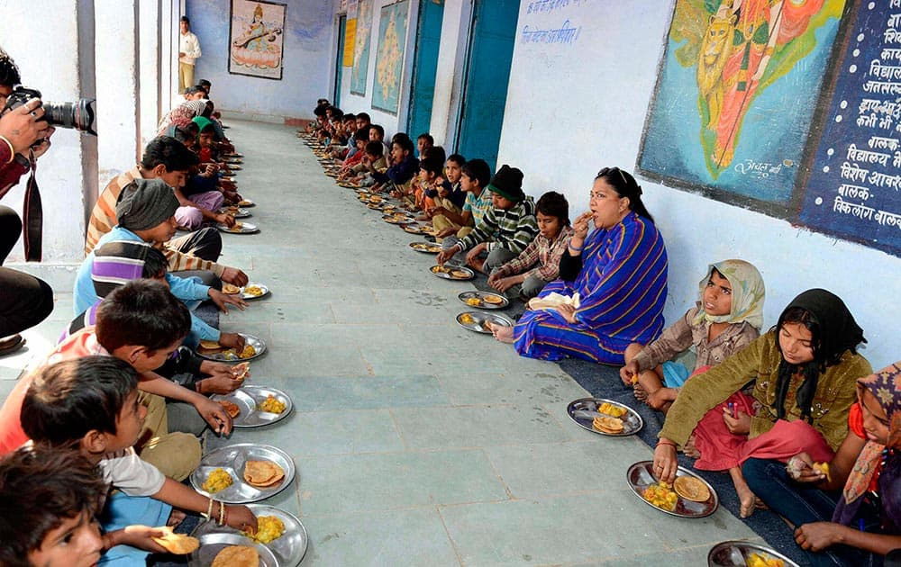 Rajasthan Chief Minister Vasundhara Raje having meals with school children during her visit in Dholpur, Rajasthan.