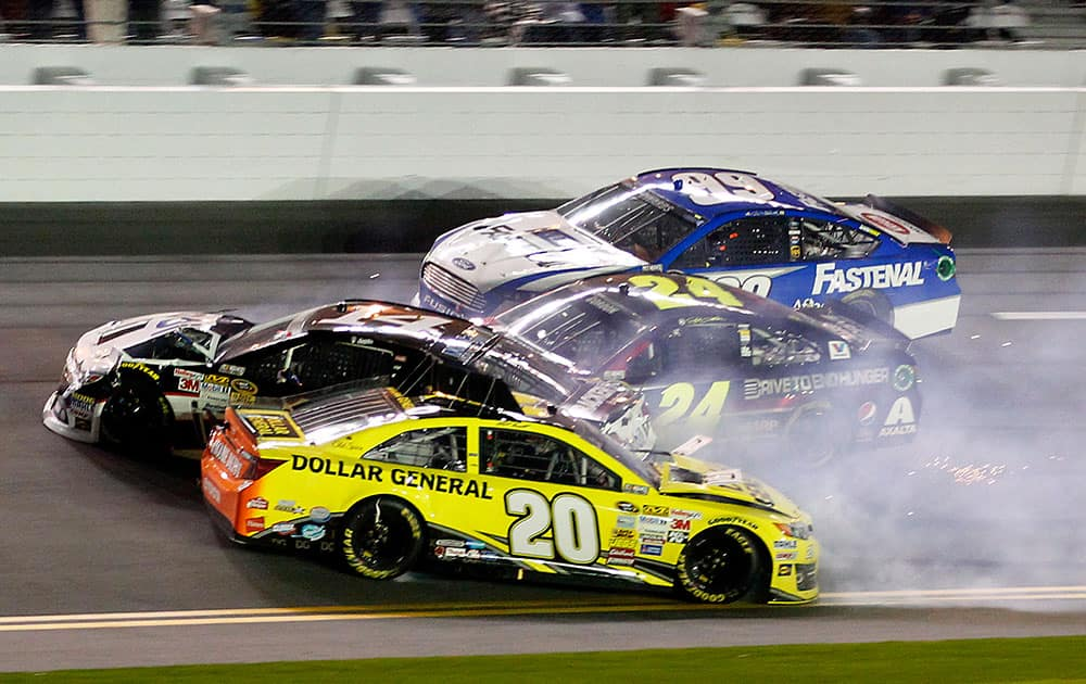 Matt Kenseth (20) slides backward as he is involved in a crash with Tony Stewart (14), Jeff Gordon (24) and Carl Edwards (99) on the front stretch during the NASCAR Sprint Unlimited auto race at Daytona International Speedway in Daytona Beach, Fla.