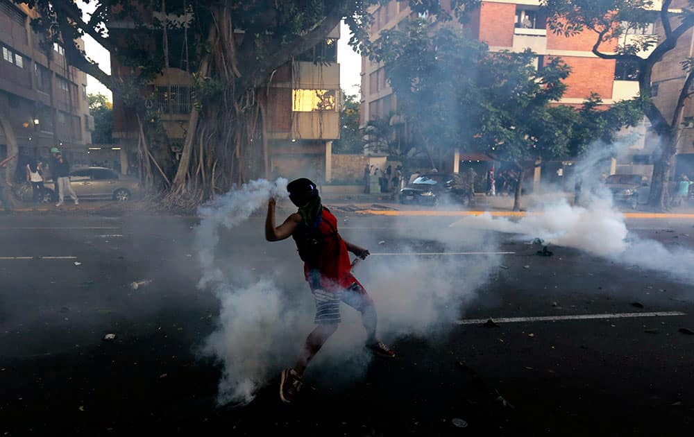 A demonstrator throws back a tear gas canister fired by the National Bolivarian Police(BNP) in Caracas, Venezuela.