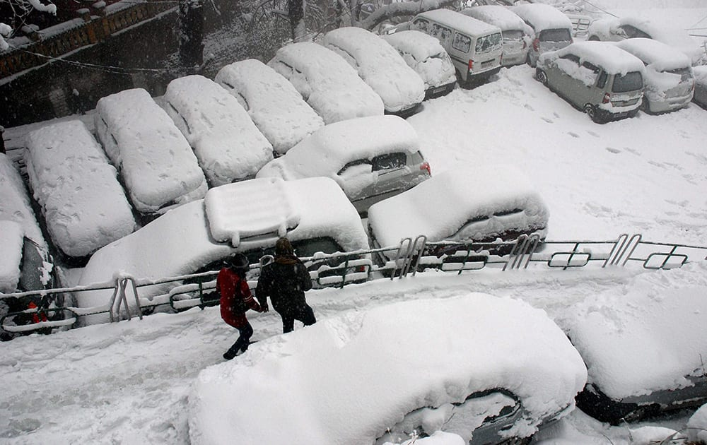 Vehicles covered with snow during a heavy snowfall in Shimla.